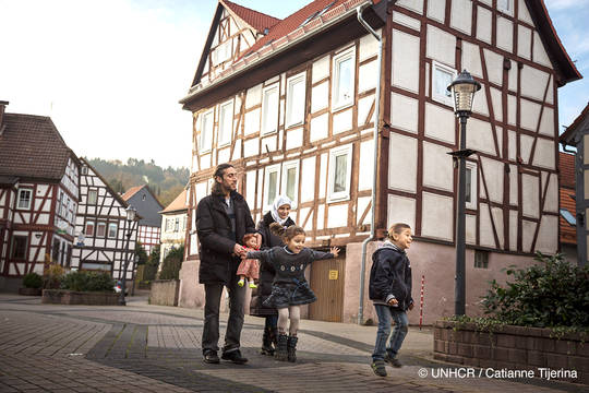 An escaped family of four walks through a small German town.